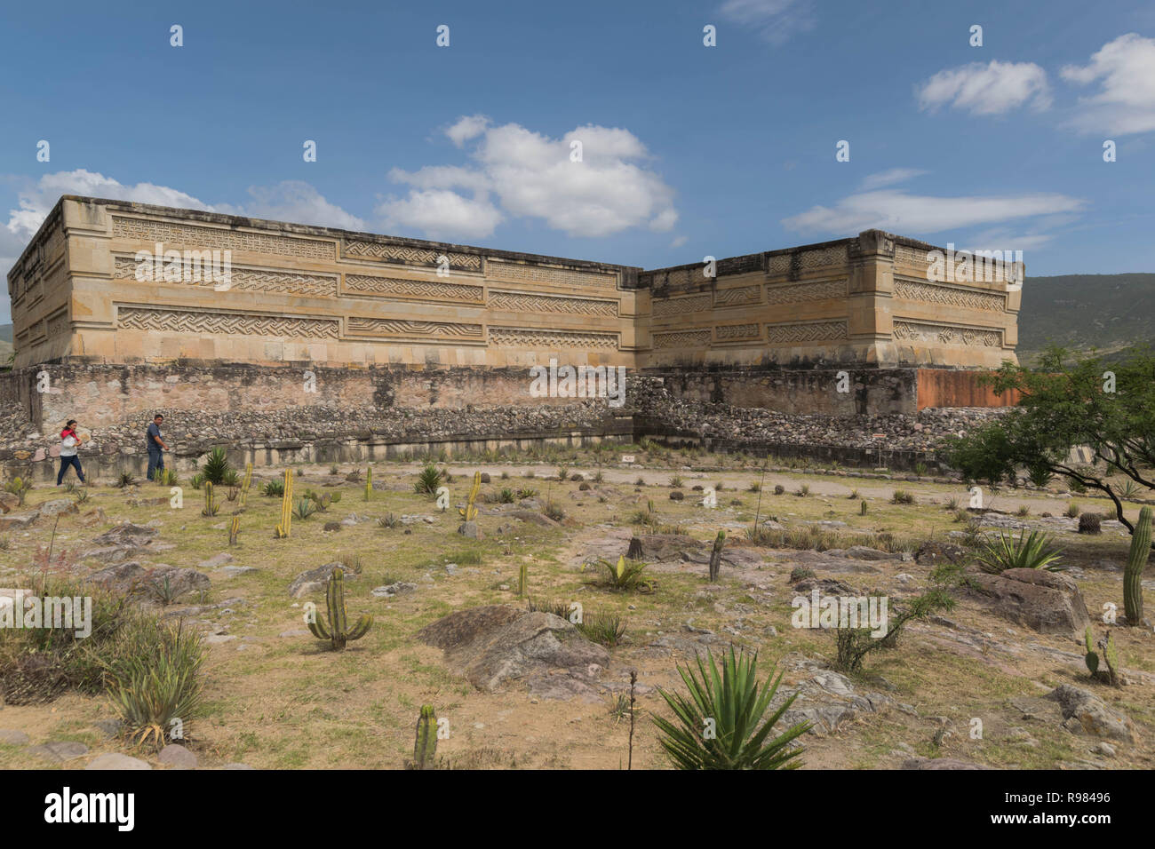 Ruins at Mitla, with dry landscape, many cactus and a cloudy blue sky, in Oaxaca, Mexico - Stock Image