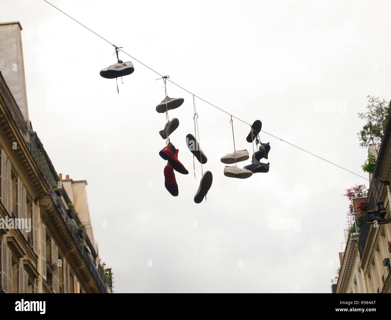 Sneakers hanging over a street in Paris, France - Stock Image