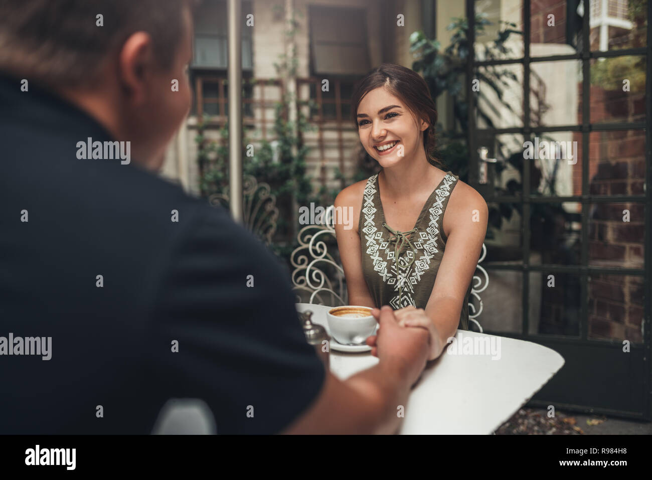Beautiful generation z girl holding hands with her boyfriends in a elegent cafe for breakfast - Stock Image