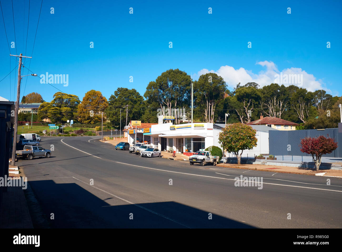 View of the road through Dorrigo with no traffic, vehicles parked in front of buildings and gum trees in the background on an autumn day - Stock Image
