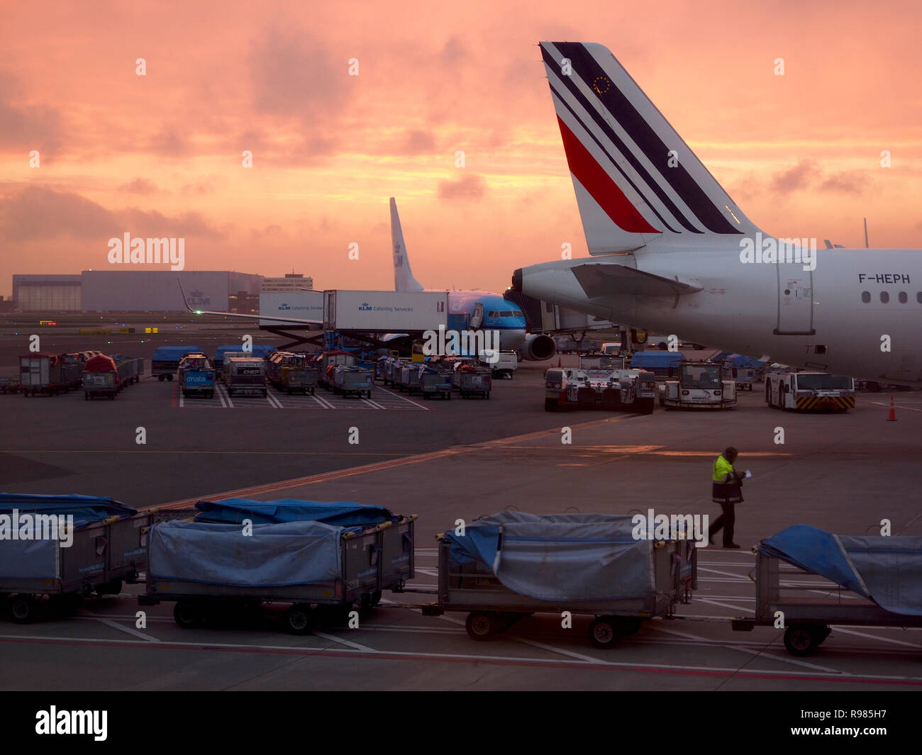 Schiphol Amsterdam Airport at sunrise early in the morning, with aeroplanes and bagage luggage cars KLM Air France - Stock Image