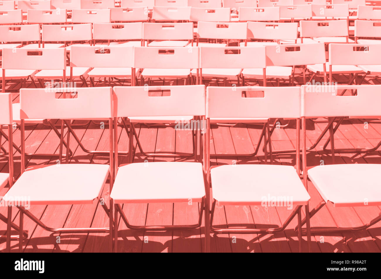 Rows of plastic chairs of coral color inspired py color of 2019. - Stock Image