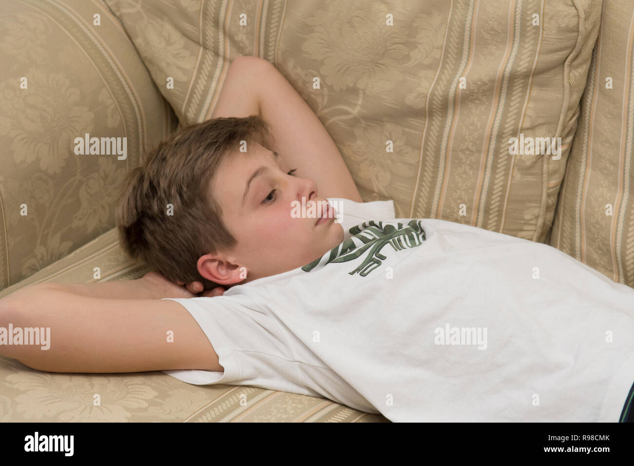 lethargic bored sullen moody lazy twelve-year-old boy laying on a sofa - Stock Image