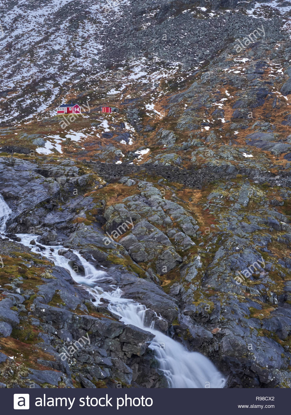 The little red house at the mountain wall close to The Troll Road Cafe in Norway - Stock Image