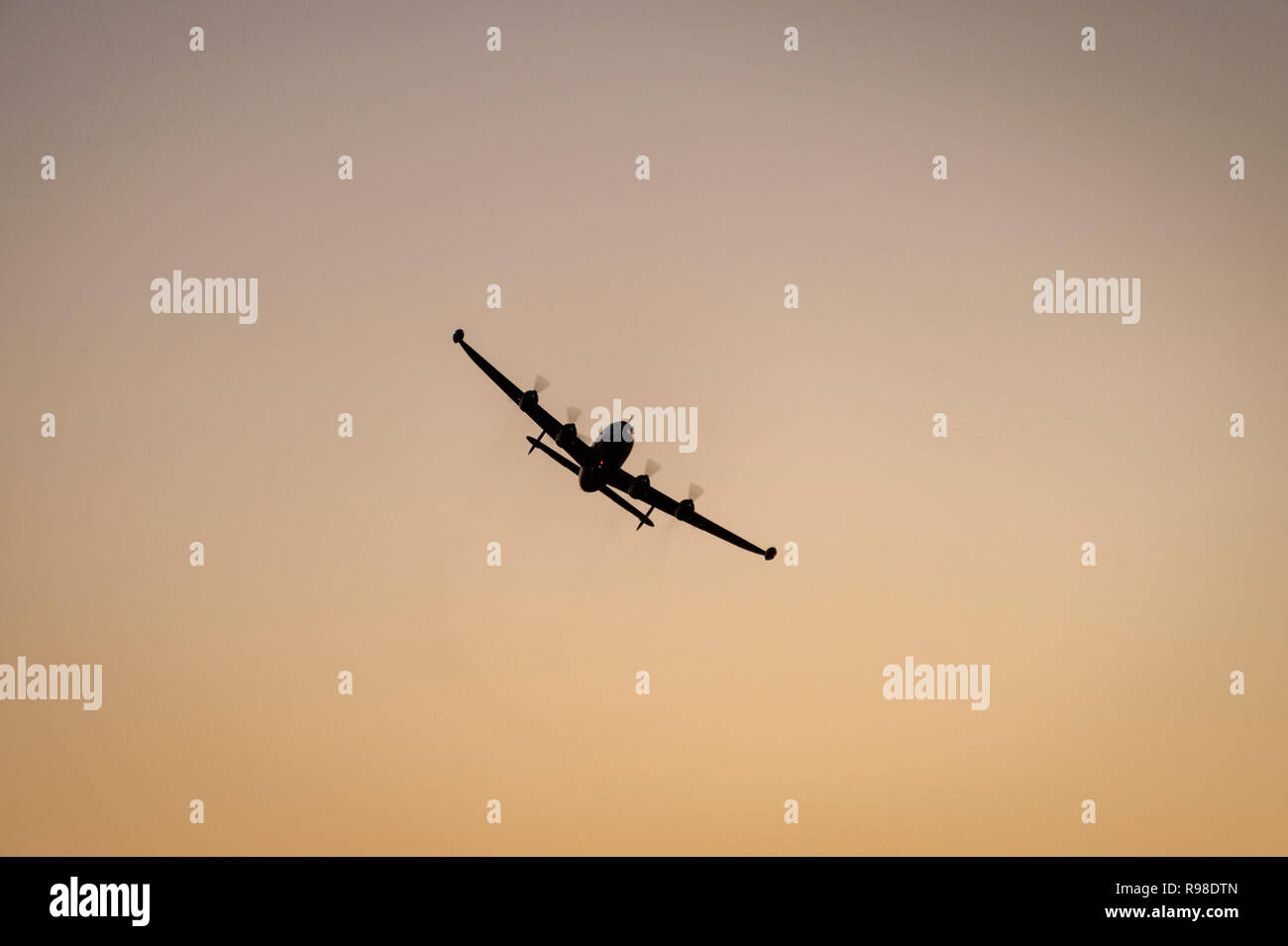 Vintage four prop passenger airplane in silhouette against an orange evening sunset - Stock Image