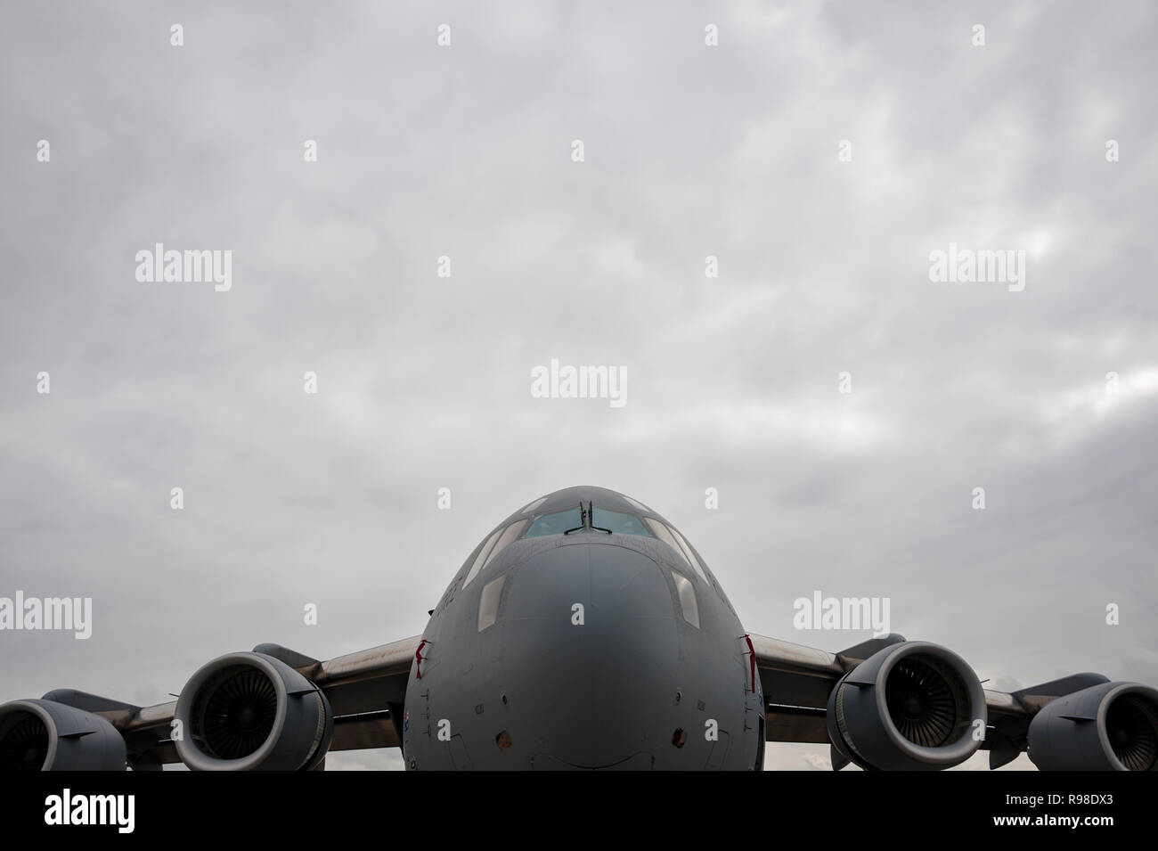Modern military cargo jet, low and symmetrical in frame with cloudy sky, negative space - Stock Photo