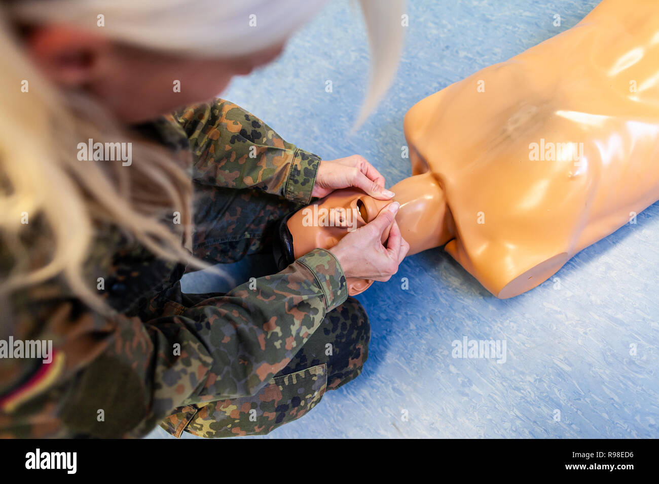Paramedical soldier practices a medical training on a puppet Stock Photo