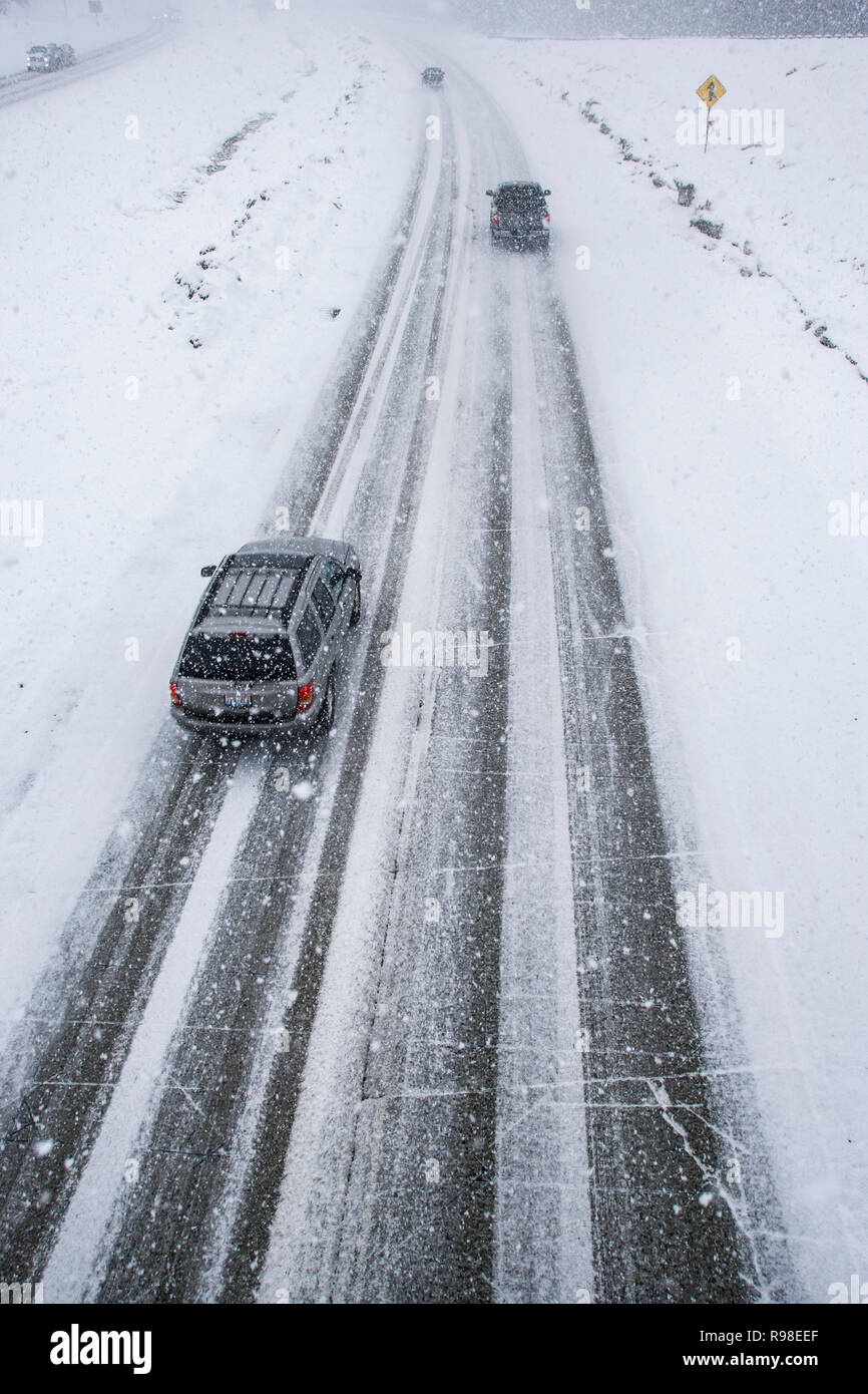 An overhead shot looking down onto a freeway road in icy snowing conditions. This is Snoqualmie Pass on I90 over the Cascade mountains in Winter. - Stock Image