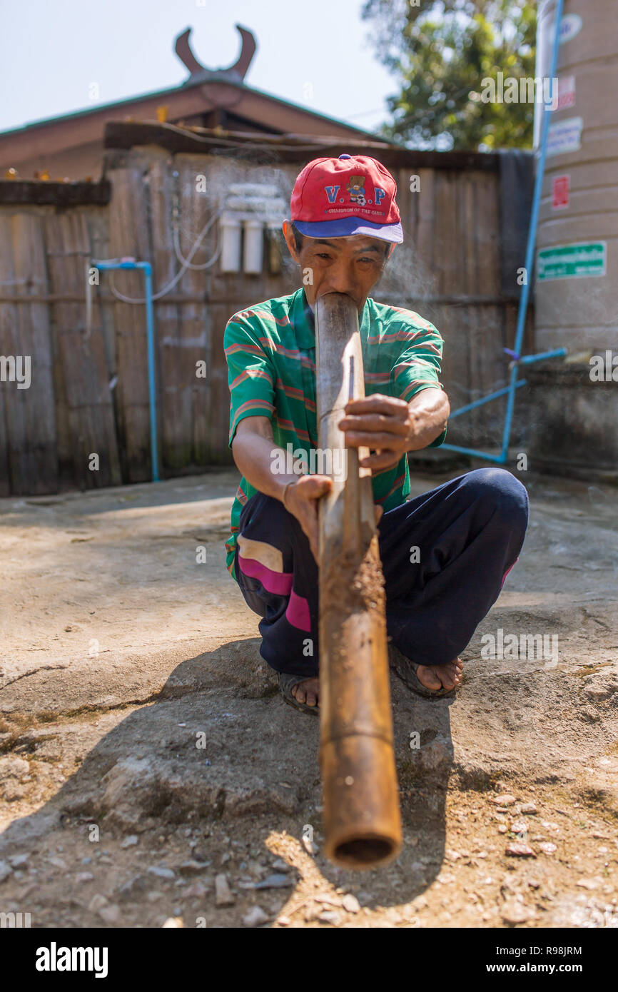 Chiang Rai, Thailand - February 8, 2017: Unidentified elderly Akha man is smoking traditional tobacco pipe in Akha hilltribe village in Northern Thail - Stock Image