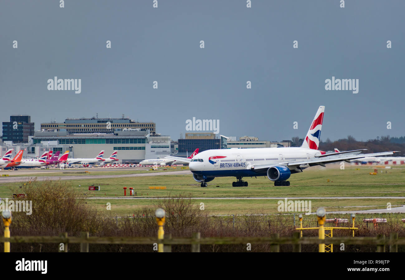 GATWICK AIRPORT, UK – DECEMBER 09 2018: A British Airways plane taxis after landing at London Gatwick Airport with airport buildings in the background - Stock Image