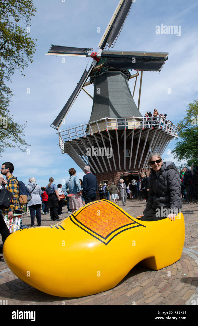 Female tourist sits in copy of yellow clog in front of a windmill in the  Keukenhof Park the world's largest bulb garden  Lisse, Holland, Netherlands Stock Photo