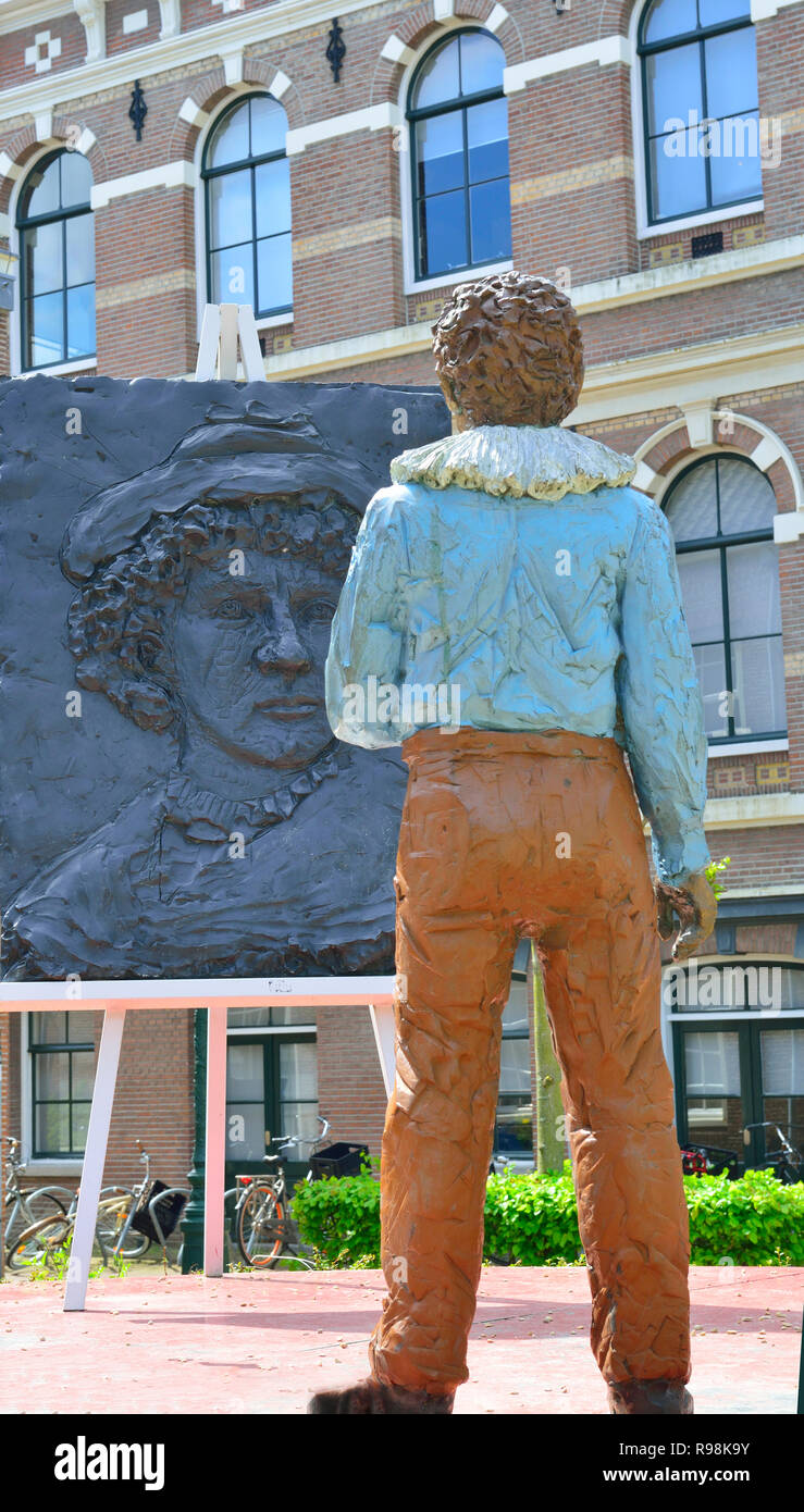 Statue of Rembrandt van Rijn working on a painting at the place he was born (house no longer there)  in the city of Leiden, South Holland, Netherlands Stock Photo