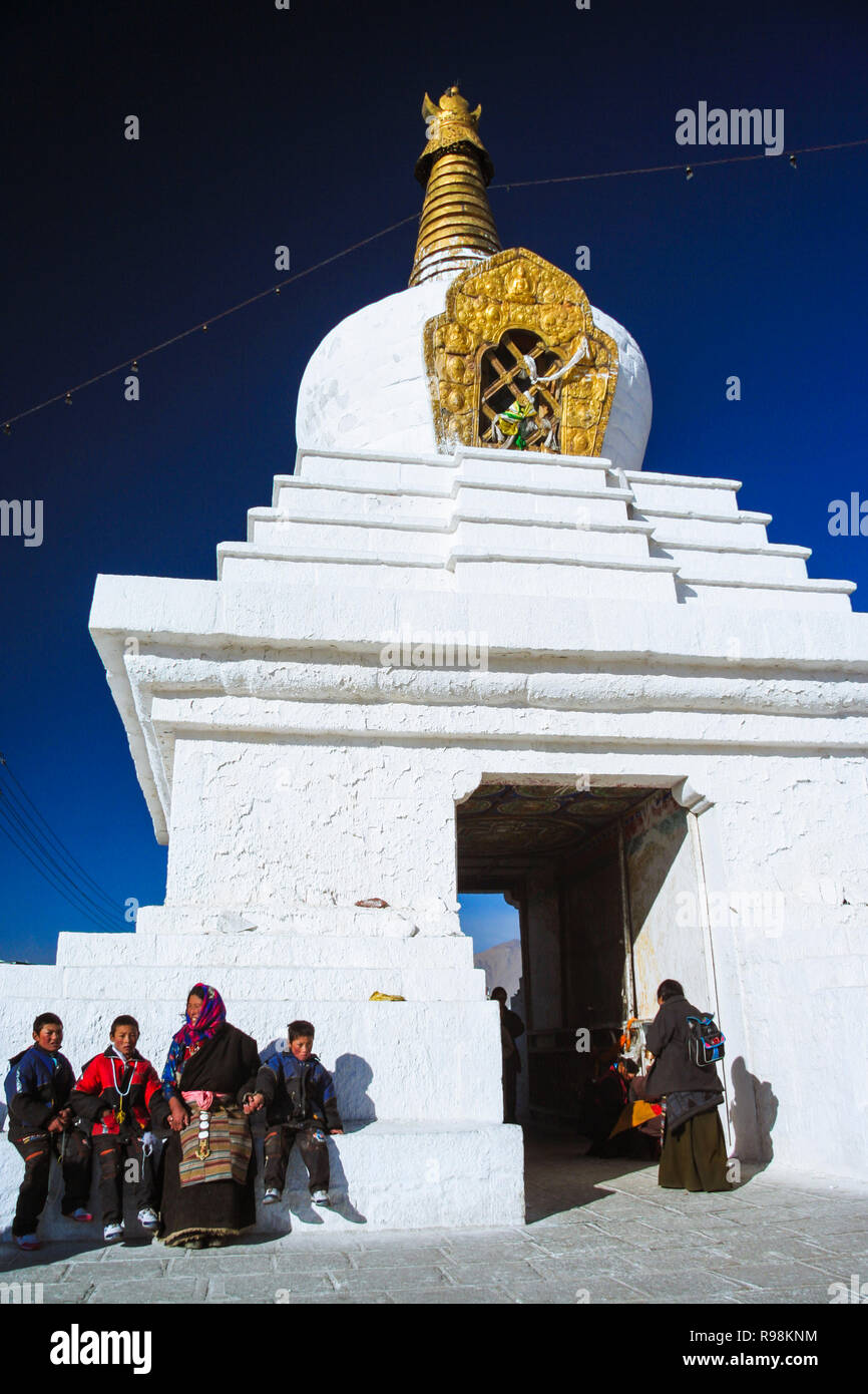 Lhasa, Tibet Autonomous Region, China : Tibetan pilgrims sit outside a Buddhist stupa. - Stock Image