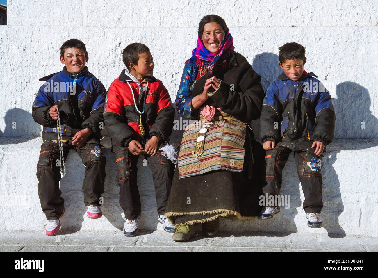 Lhasa, Tibet Autonomous Region, China : A Tibetan pilgrim family sit outside a Buddhist stupa. - Stock Image