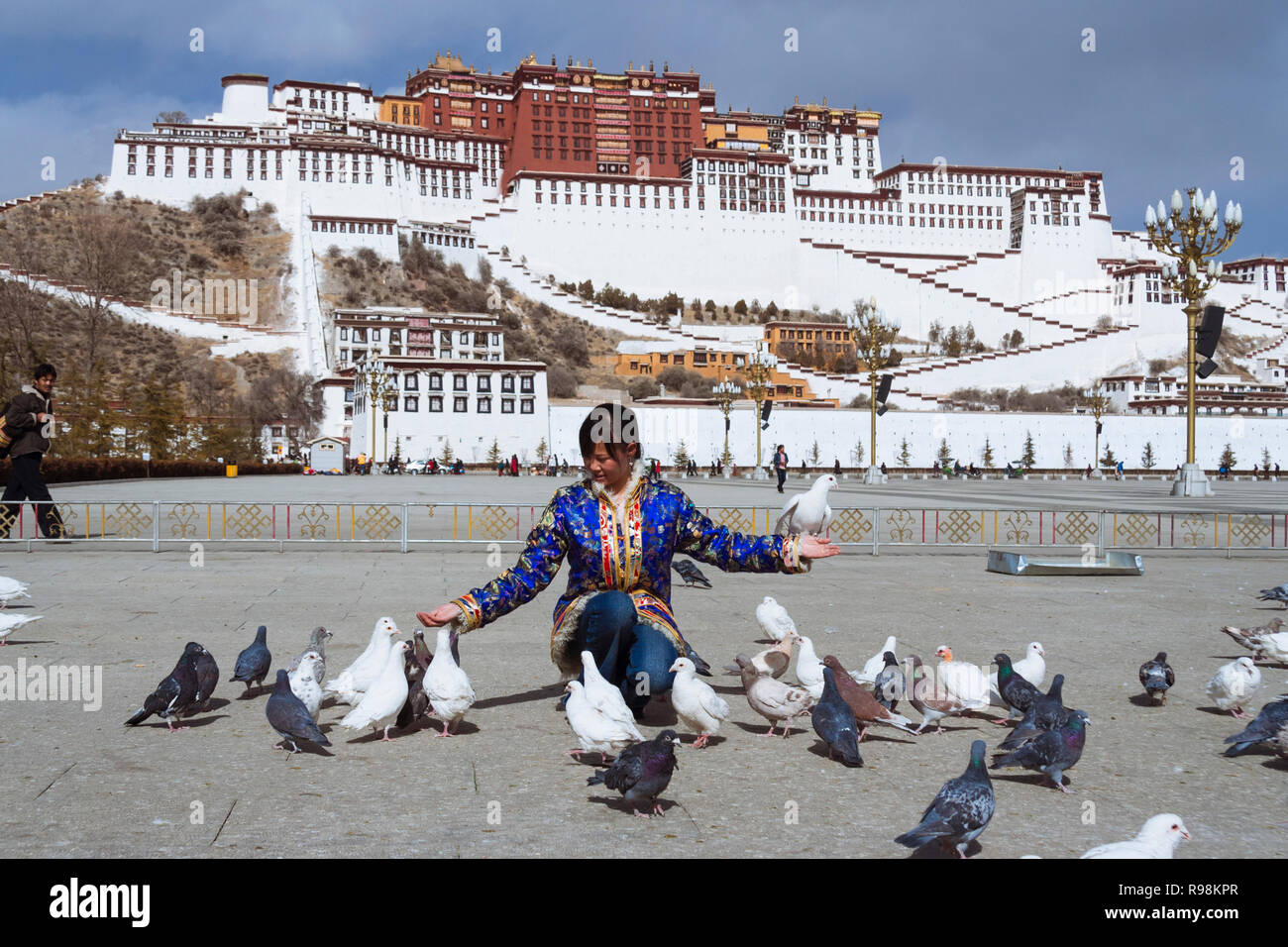 Lhasa, Tibet Autonomous Region, China : A young woman feeds the pigeons at Potala Square in front of the Potala Palace. First built in 1645 by the 5th Stock Photo