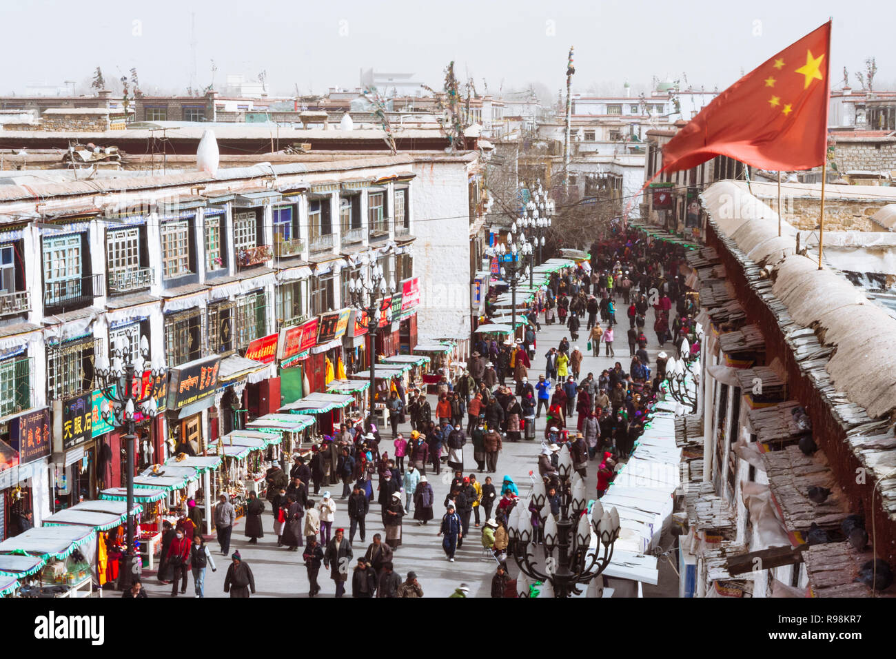 Lhasa, Tibet Autonomous Region, China : A Chinese flag waves over the people walking along one of the main streets of the Barkhor district. - Stock Image