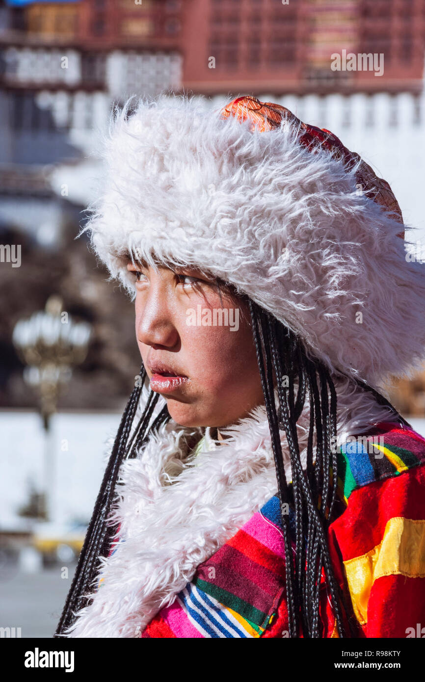 Lhasa, Tibet Autonomous Region, China : Portrait of Young Tibetan woman in traditional costume next to Potala palace. First built in 1645 by the 5th D - Stock Image