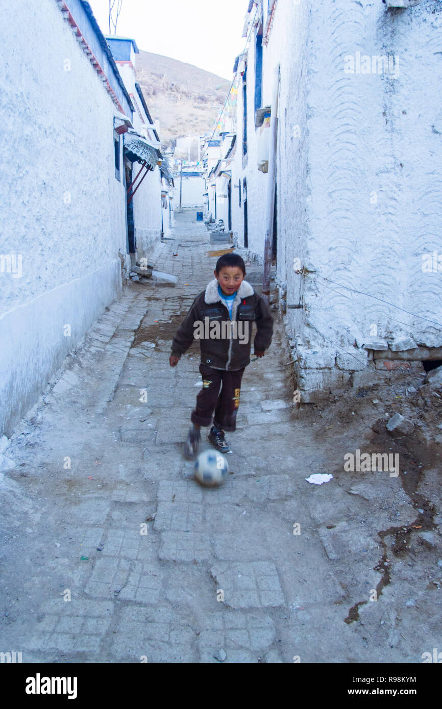 Shigatse, Tibet Autonomous Region, China : A child runs with a ball in the whitewashed alleys of the old town of Shigatse. - Stock Image