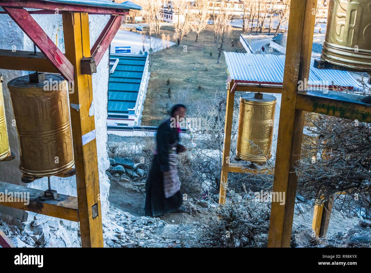 Shigatse, Tibet Autonomous Region, China : A Buddhist pilgrim walks past prayer wheels on the lingkhor (sacred path)circumambulating the walls of Tash - Stock Image