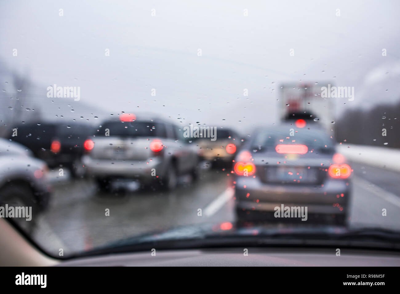 Looking out the wet windshield of a car at other cars  on a crowded roadway. - Stock Image
