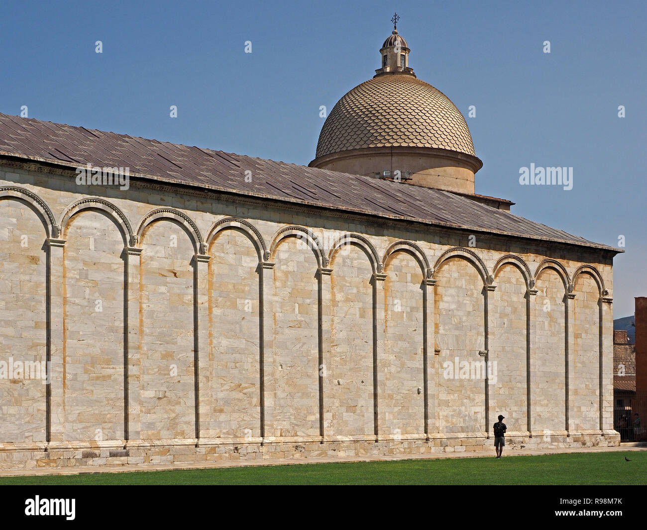 A single tourist viewing the dome above the Campiosanto cemetery is dwarfed by the structure in Pisa,Tuscany,Italy - Stock Image