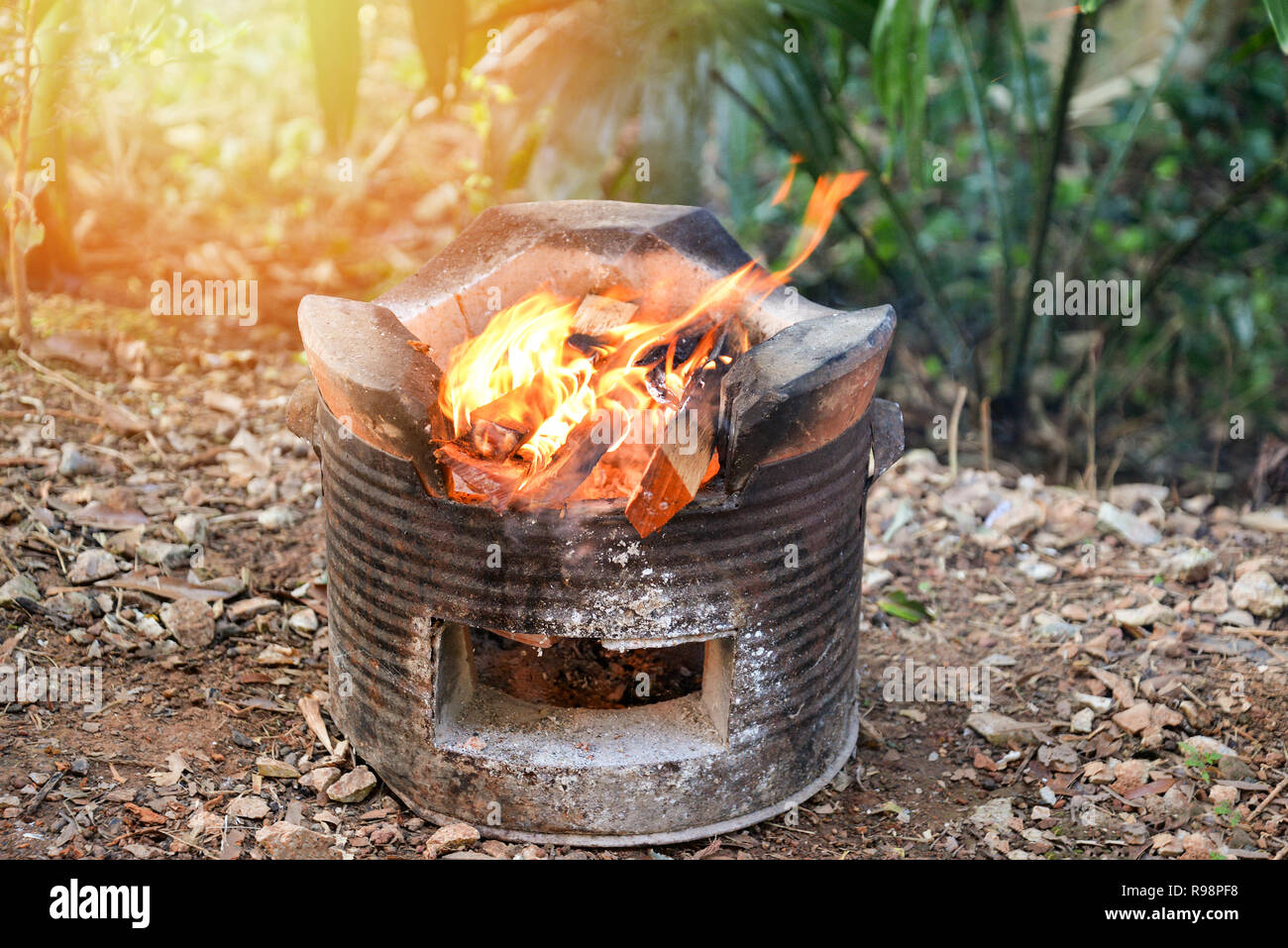 stove fire outdoors / bonfire on old stove baked clay with firewood burn for cooking in camping - stove asia - Stock Image