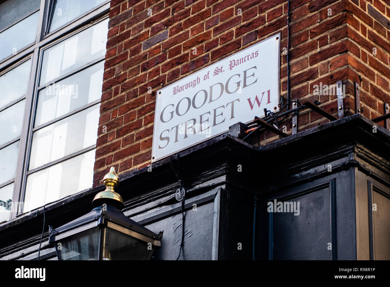 Looking at the corner of a brick building showing a Goodge Street road name sign high up on a brick wall in London - Stock Image