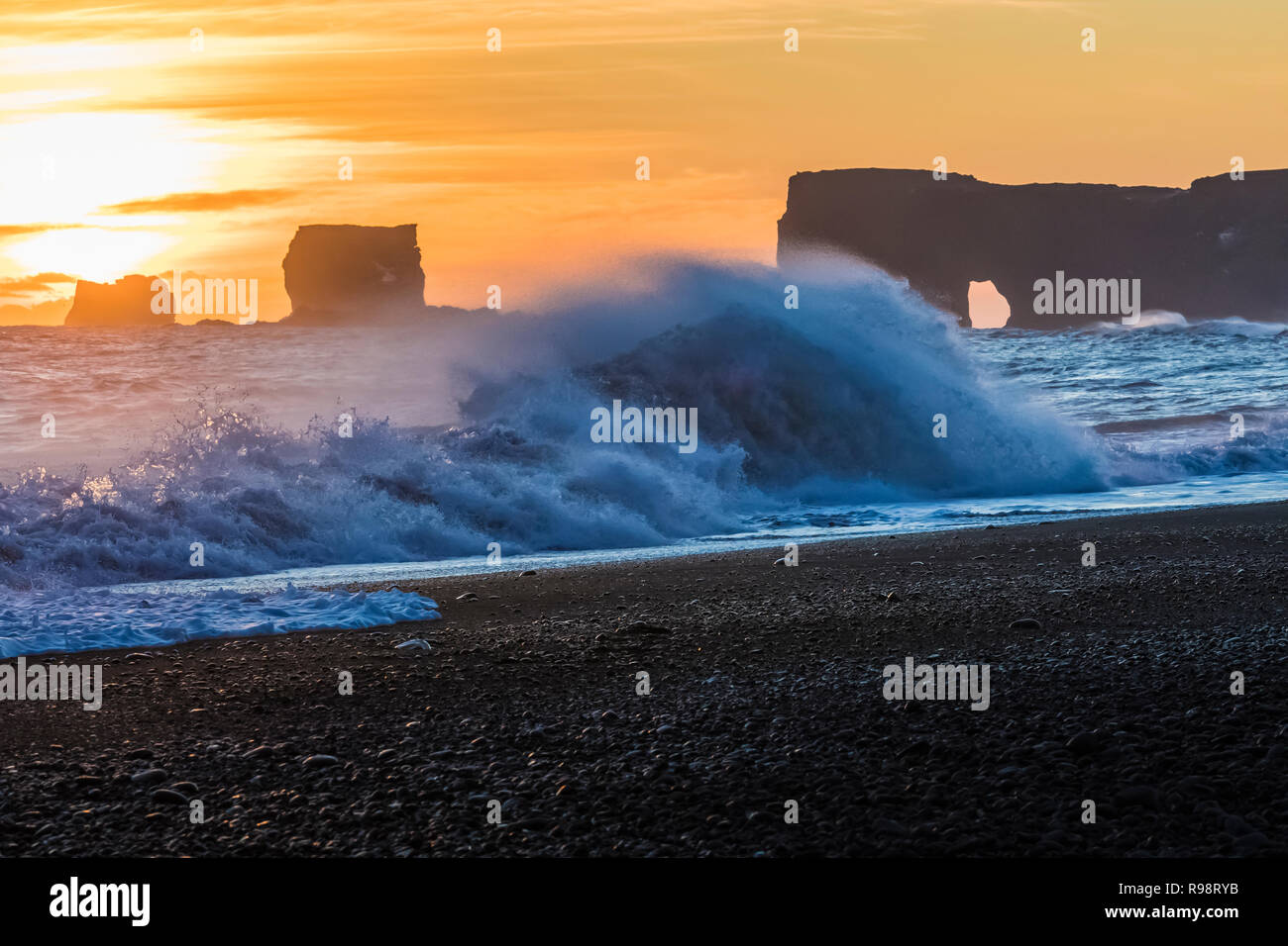 Waves crashing at sunset with Dyrhólaey, a rock with an arch