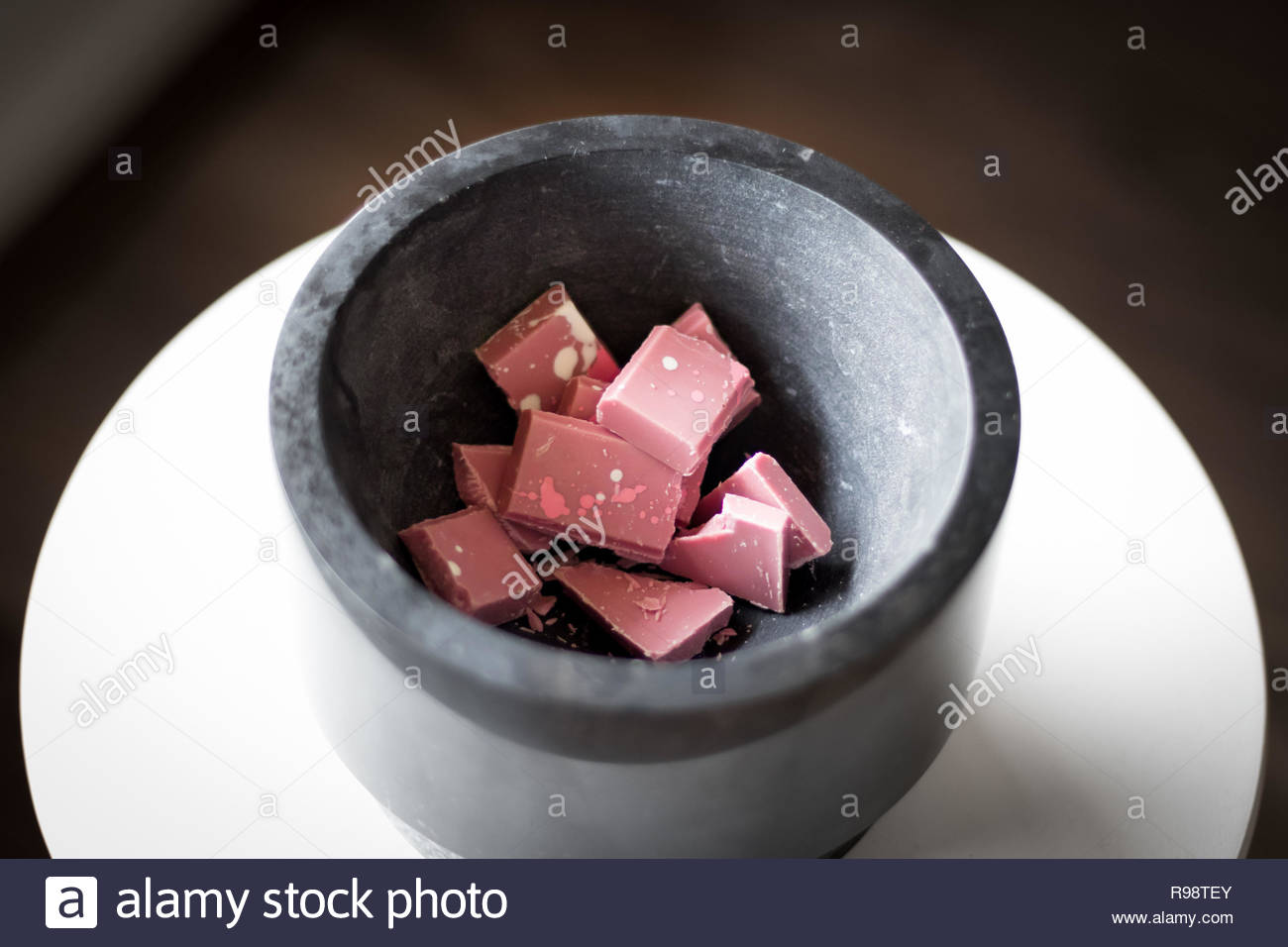Broken and shattered pieces of ruby red chocolate in a round charcoal stone ceramic bowl. White and brown background. Speckled chocolate. - Stock Image