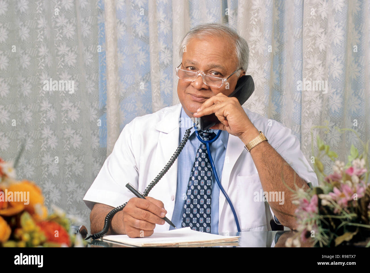 old age seniors male doctor holding telephone receiver and listening MR.No.320 - Stock Image