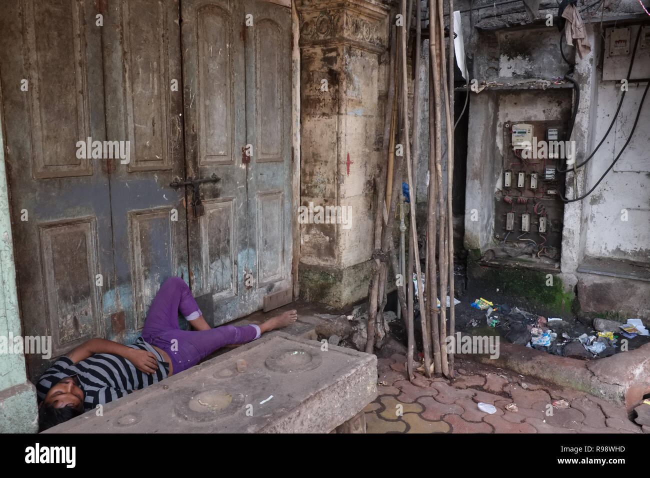 A man sleeps in a doorway in Mumbai, India, next to to a dubious looking electric unit counter and transformer - Stock Image