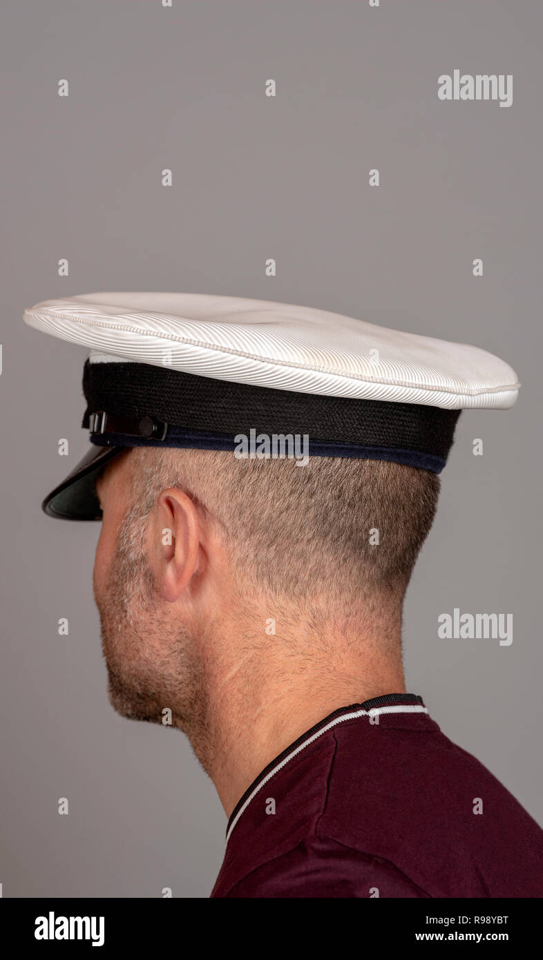 Naval officer with short hair and military uniform cap - Stock Image