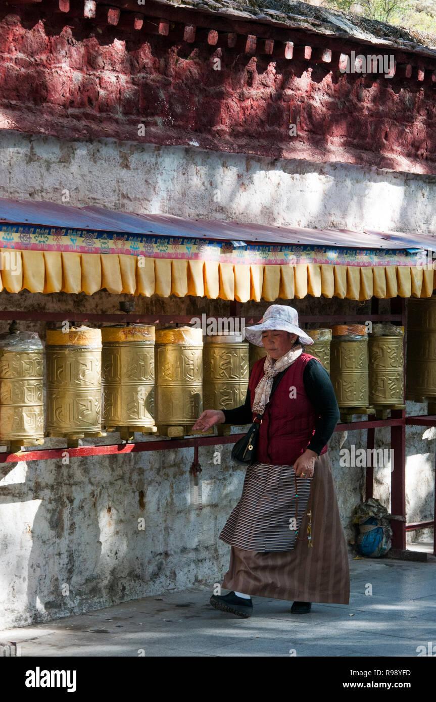 A female pilgrim rotates prayer wheels along the kora or pilgrimage path below the Potala Palace, Lhasa, Tibet, China - Stock Image