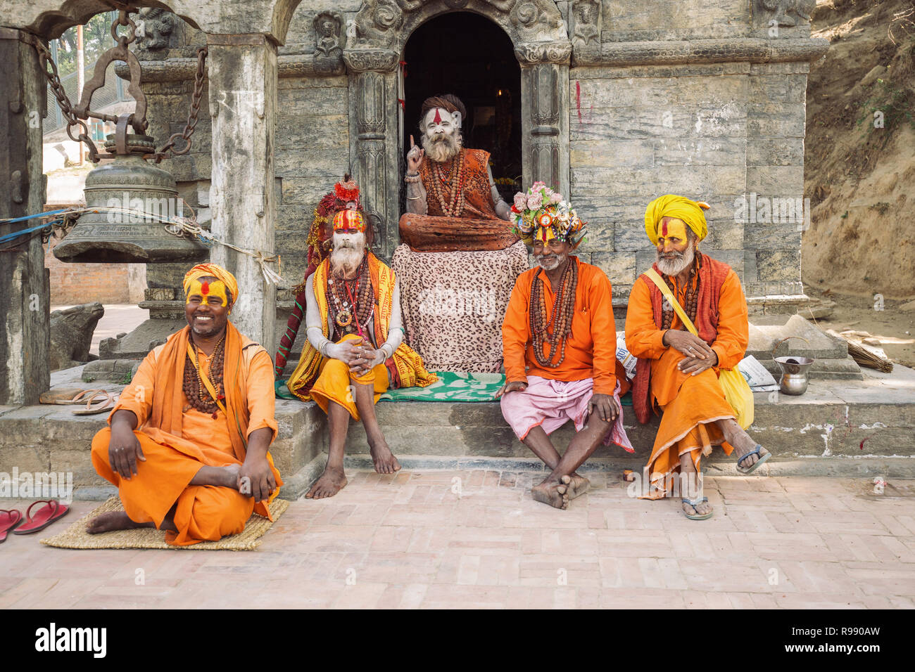 Sadhus posing with tourist at Pashupatinath Temple. In Hinduism, the sadhu is solely dedicated to achieving moksha through meditation and contemplatio - Stock Image