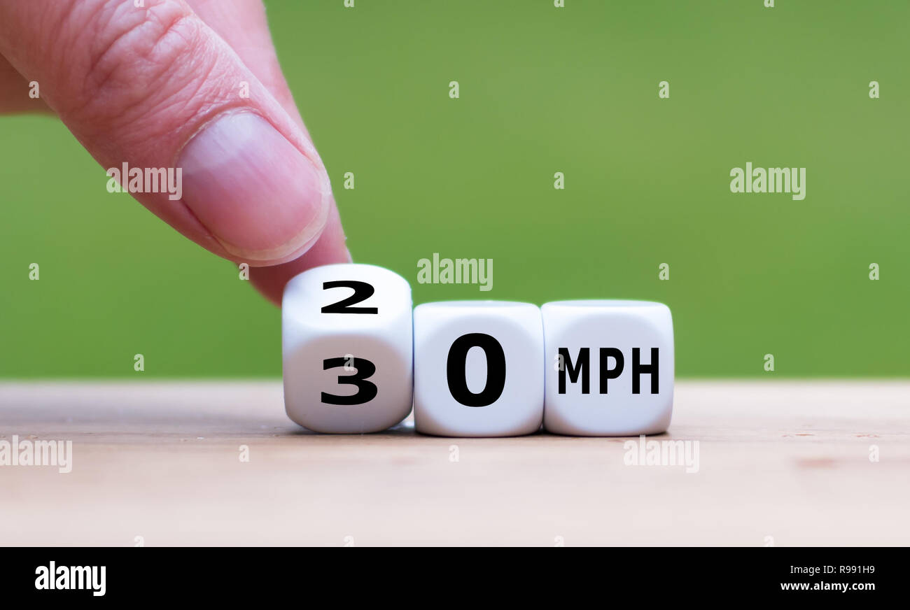 "Hand is turning a dice and changes the expression ""50 MPH"" to ""30 MPH"" as symbol to reduce the speed limit from 50 to 30 miles per hour Stock Photo"