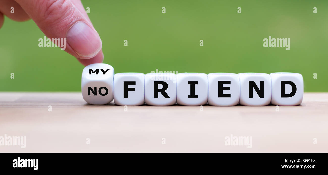 Hand is turning a dice and changes the expression 'no friend' to 'my friend' - Stock Image
