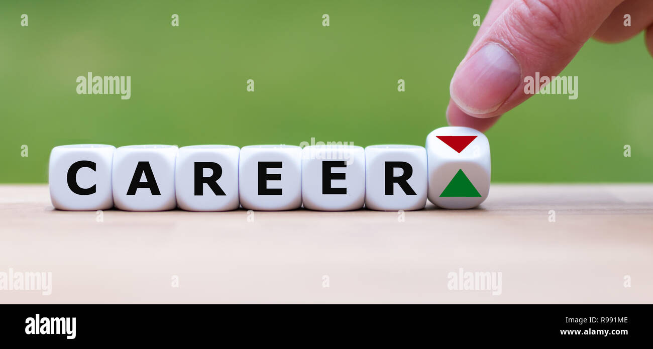 Hand is turning a dice and changes the direction of an arrow symbolizing that the career goes into a positive direction - Stock Image