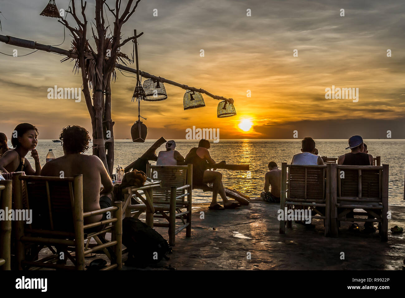 An outdoor bar on a cliff with young people relaxing with their drinks in the sunset, Haad Son, Koh Pangan, Thailand, May 8, 2016, Stock Photo