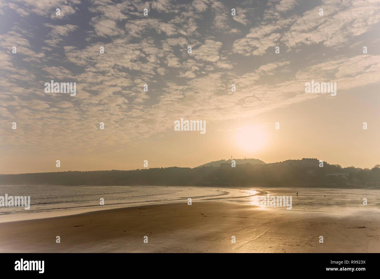 The beach and coast at Scarborough looking into the sun. The empty beach stretches out to a headland and a cloud filled sky is above. - Stock Image