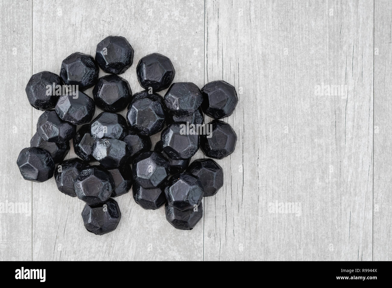 Pile of coal shaped candy on a gray washed wood background, as a naughty for Christmas concept Stock Photo