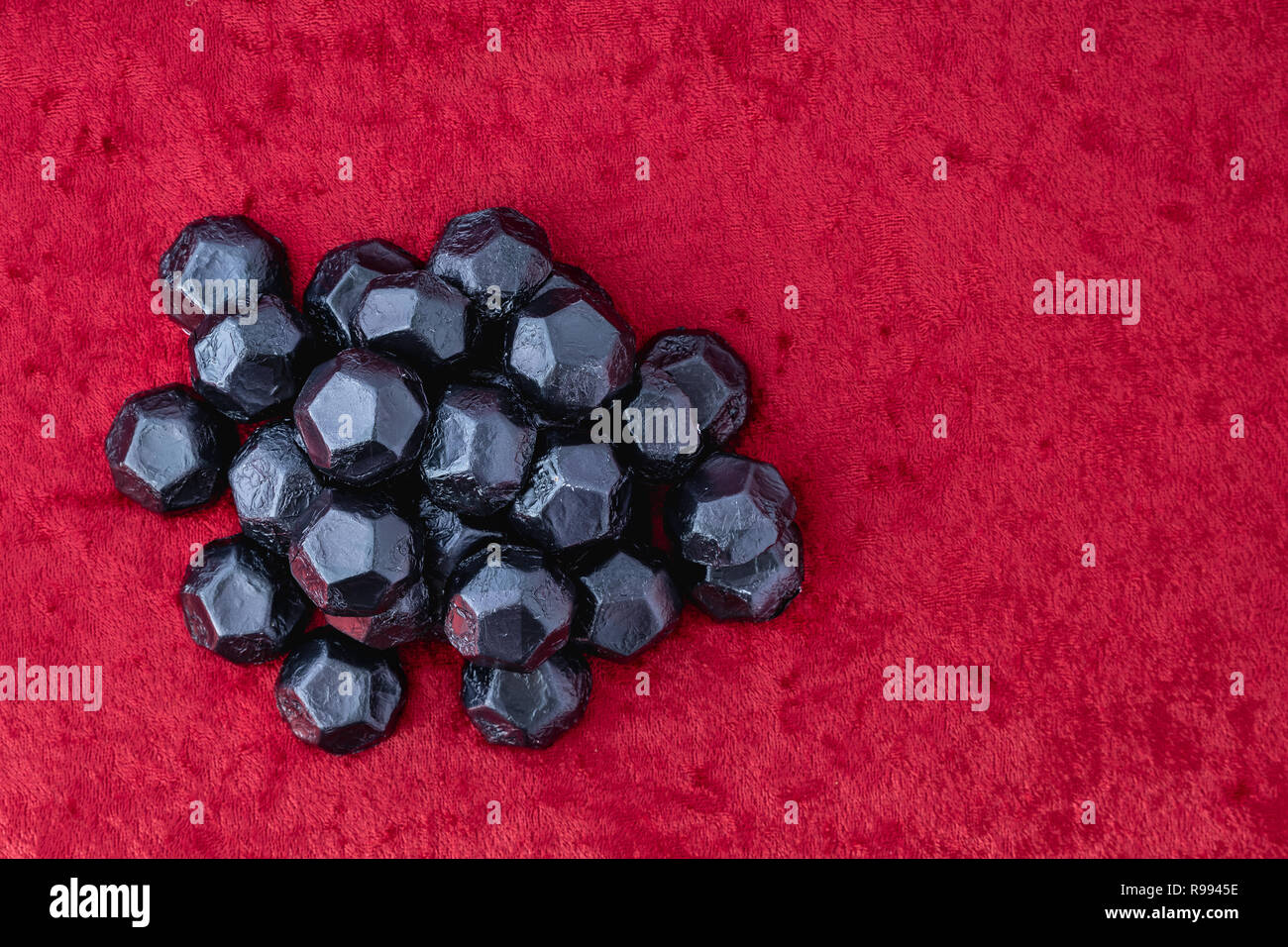 Pile of coal shaped candy on a red velvet background, as a naughty for Christmas concept Stock Photo