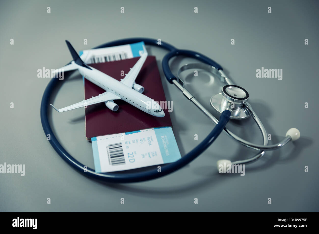 travel insurance - passport with flight ticket and stethoscope on gray background - Stock Image