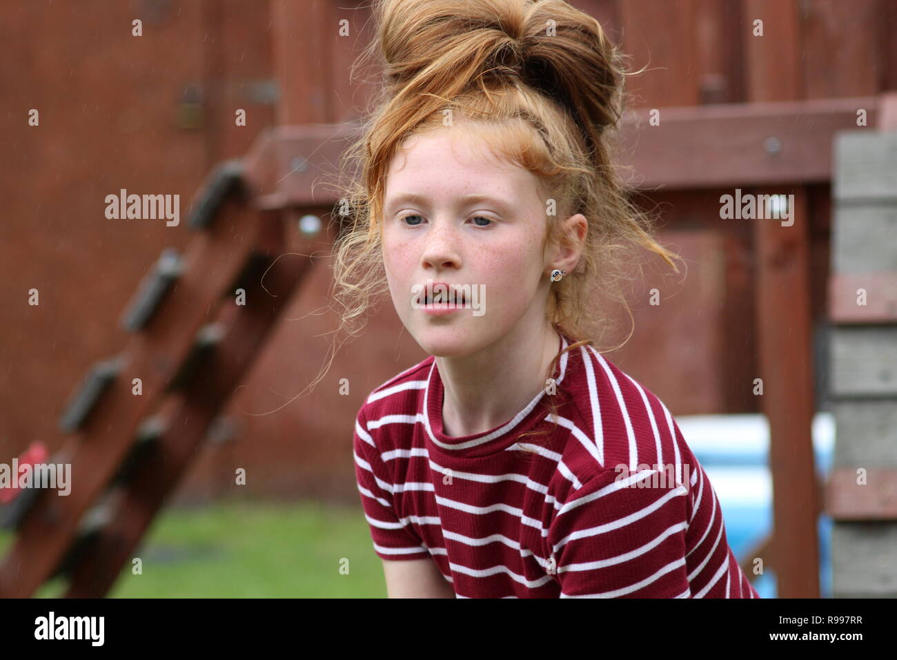 10 year old ginger child outside in the garden, Manchester - Stock Image