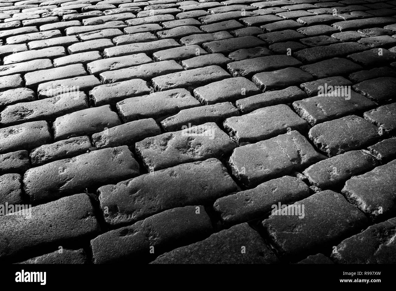 Cobblestone background with long shadows at sunset, London - Stock Image