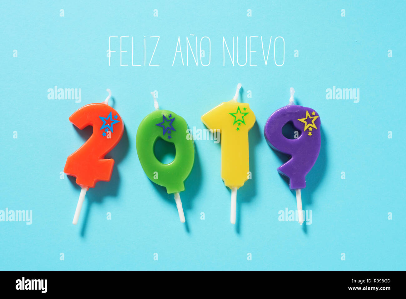 high angle view of some number-shaped candles of different colors forming the number 2019, and the text feliz ano nuevo, happy new year written in spa - Stock Image