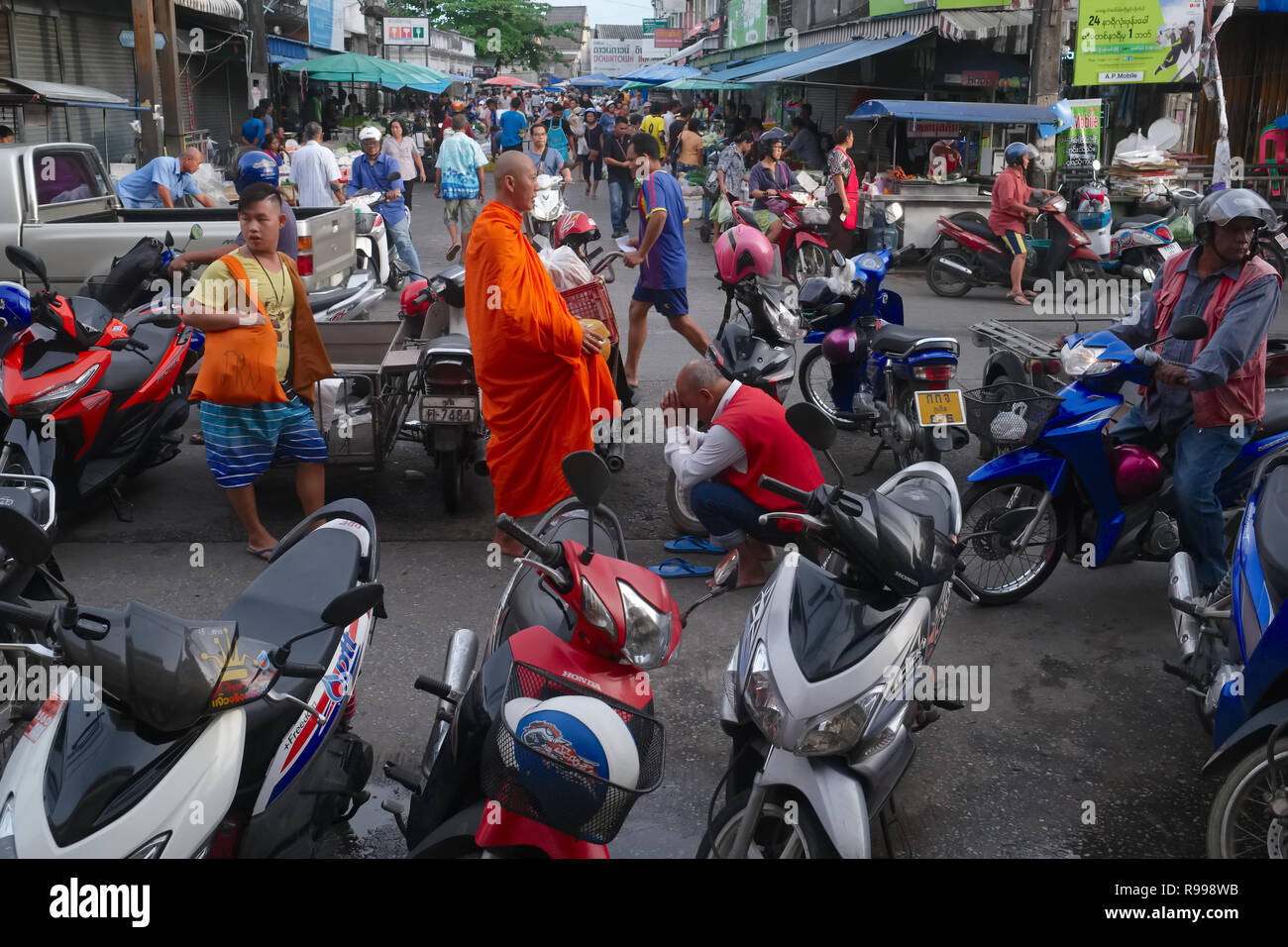 A motorcycle taxi driver in the main market in Phuket Town, Thailand, bows to a Buddhist monk and pays his respects with a traditional Thai 'wai' - Stock Image