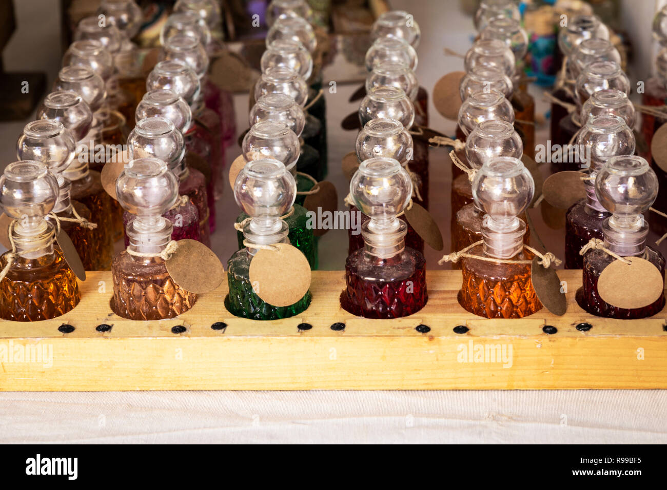 several glass jars perfume colors on a stand in a store - Stock Image