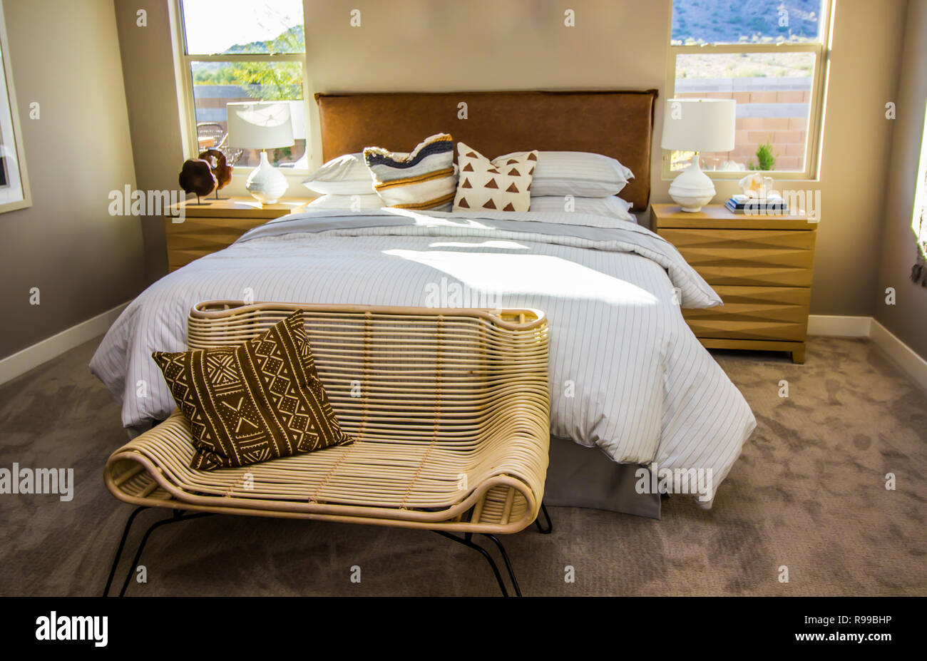 Master Bedroom With Bed Lamps Nightstands And Wicker Chair Stock