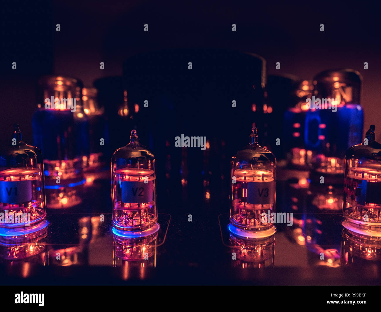 Vacuum tubes on a row, glowing in the dark. Warm colors contrasting a blue glow. - Stock Image