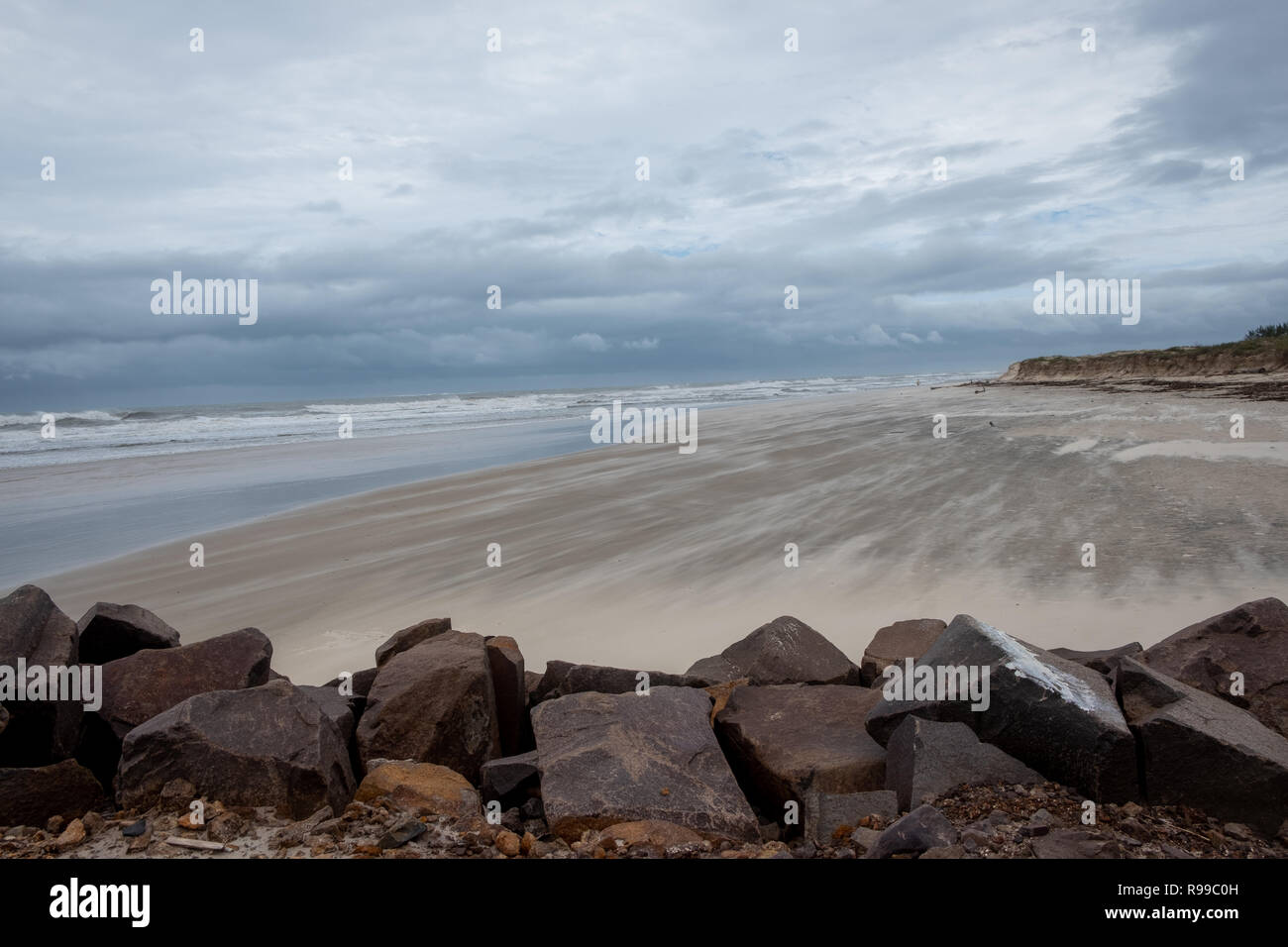 View of the beach on a very windy day in the winter season. Focus in a cluster of stones. Torres beach, Rio Grande do Sul state, Brazil. - Stock Image